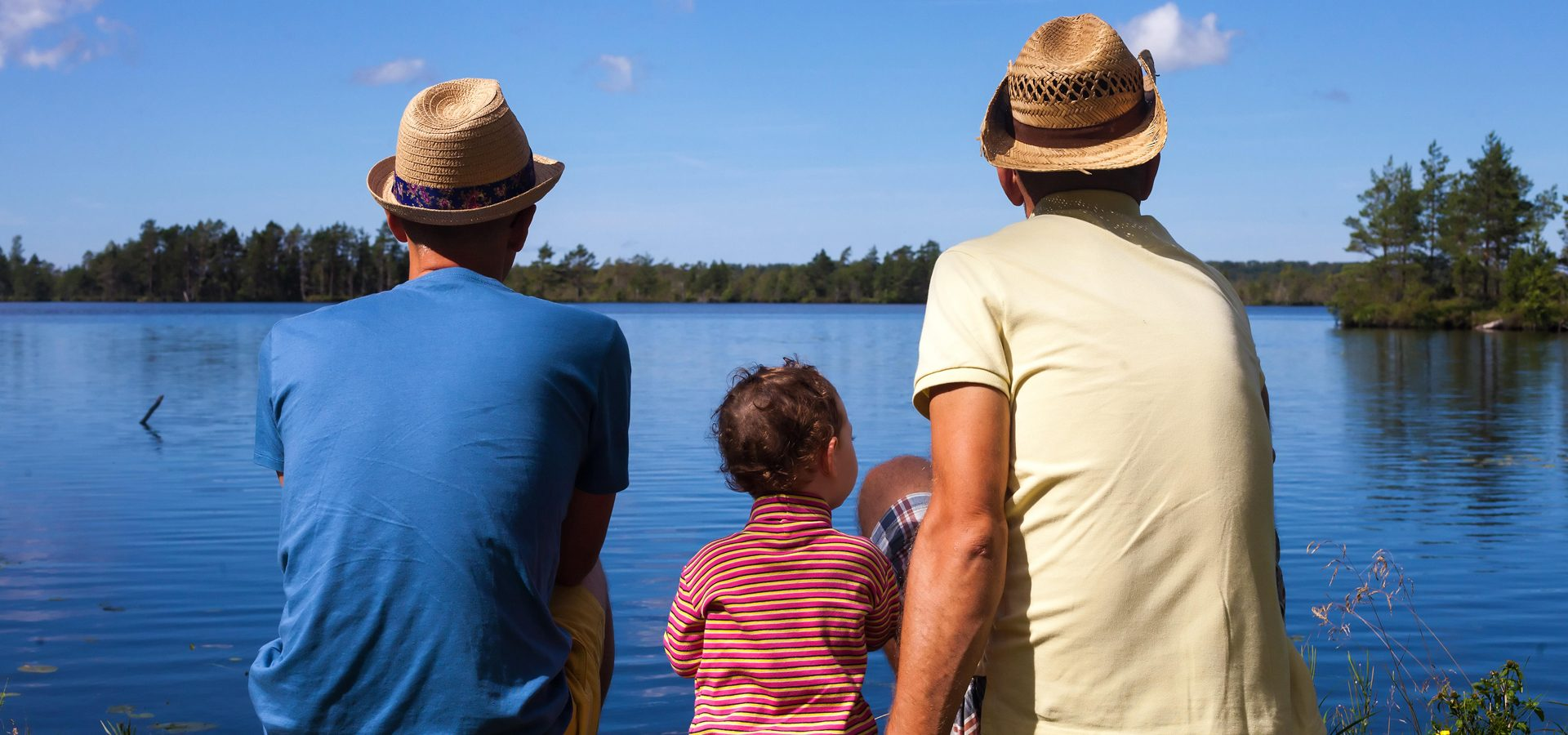 two dads and thier child looking out onto a lake